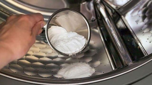 Hòa baking soda, giấm vào nước ấm trong lồng giặt, ngâm từ 30 đến 60 phút.